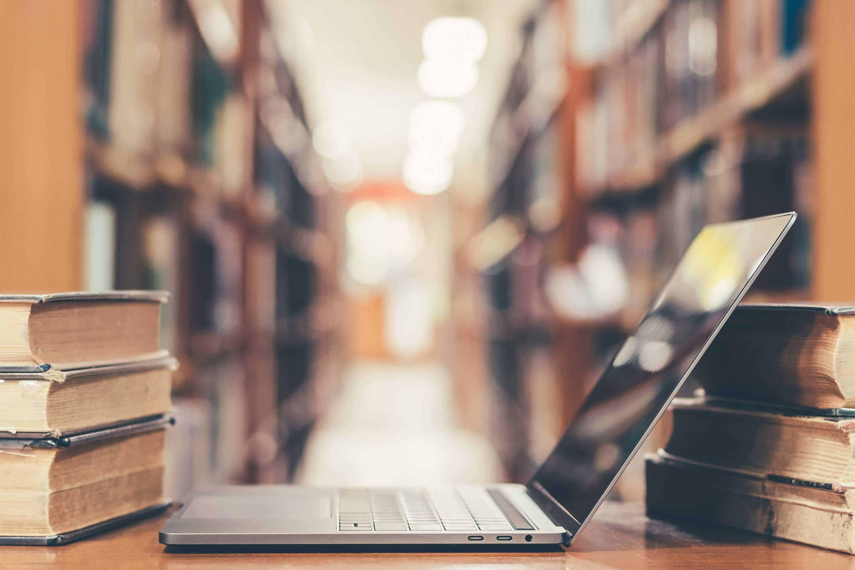 Laptop in Bibliothek als Darstellung neuer Technologien in einer Datenbank